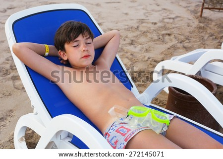 preteen handsome boy lay on the beach with snorkeling mask  get sun tan - stock photo