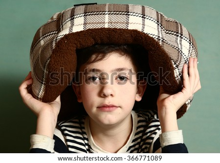 preteen handsome boy put cat bed as a hat on his head - stock photo