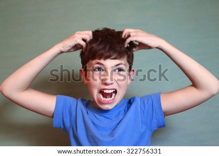 preteen handsome boy scratch his head isolated on blue - stock photo