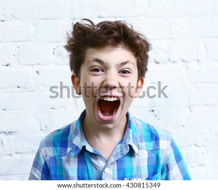 preteen handsome boy shouting yelling close up portrait on the white wall background - stock photo