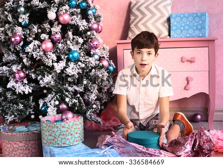 preteen handsome boy with christmas tree and presents - stock photo