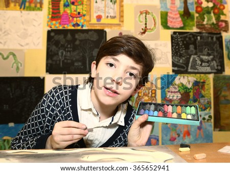 preteen handsome boy with pastel chalk in the art school classroom - stock photo