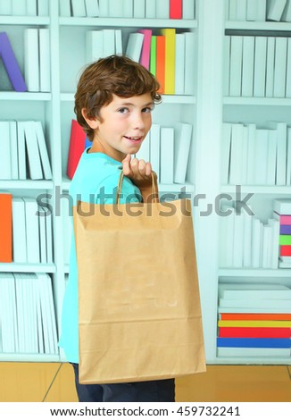 preteen handsome boy with shopping bag on the book store background