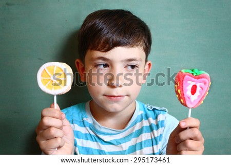 preteen handsome boy with two marsh mellow sweets on stick isolated on blue - stock photo