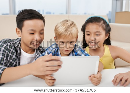Preteen kids gathered in front of digital tablet