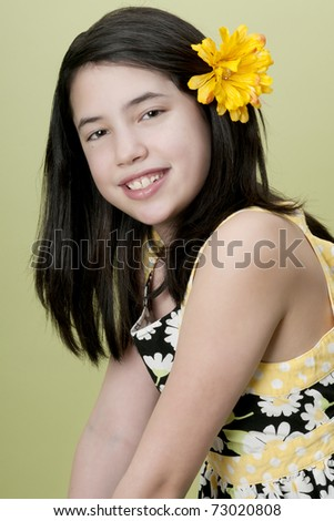 Preteen model posing with yellow flower in hair