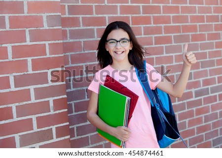 Preteenager girl next to a red brick wall with the backpack and books saying Ok - stock photo