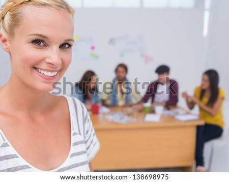Prettty editor smiling at camera as team works behind her at large desk in office - stock photo