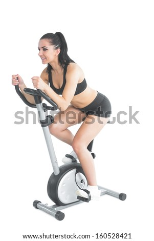 Pretty active woman training on an exercise bike on white background