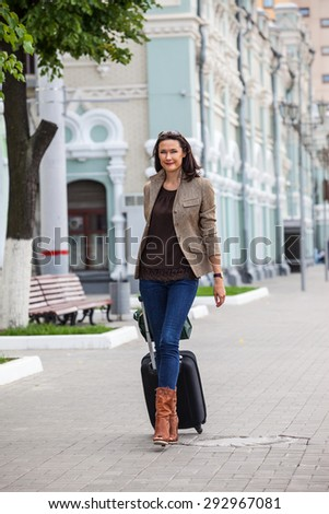 pretty adult businesswoman with a suitcase walking on the apron landside and  smiling