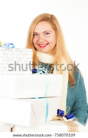 Pretty adult woman dressed in warm sweater, gloves and scarf gives a gift. Christmas, New Year and birthday celebration concept. Detailed studio shoot isolated on abstract blurred white background