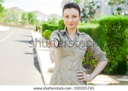 Pretty adult woman giving handshake near detached house. Real estate agent reaching agreement - stock photo