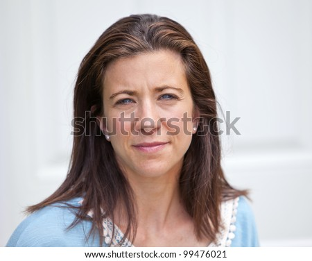 Pretty adult woman looking forward with sad expression - stock photo