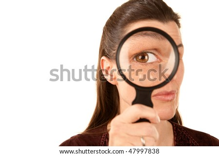 Pretty adult woman looking through magnifying glass