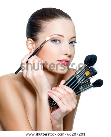 Pretty adult woman making make-up around the eyes. Model posing over white background - stock photo