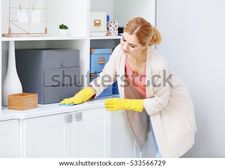 Pretty adult woman wiping furniture at home