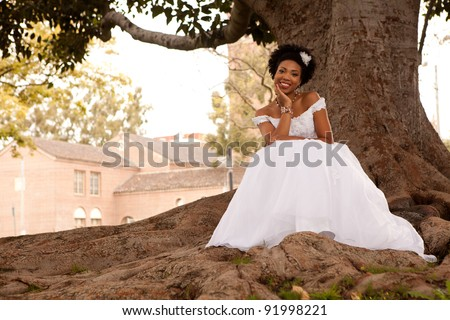 Pretty African American Bride is smiling at you in the park - stock photo
