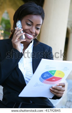 Pretty African American Business Woman on the Phone Holding Report - stock photo