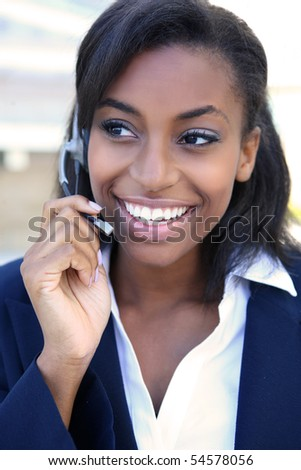 Pretty african american business woman talking on ear phone at office building - stock photo