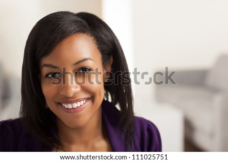 Pretty African American business woman wearing purple jacket and black shirt.