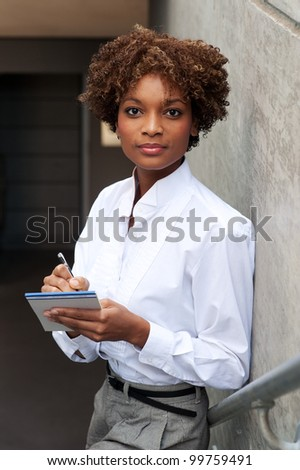 pretty African American executive sitting outside with pen and paper - stock photo