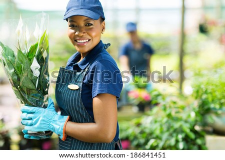 pretty african american nursery worker holding potted plant - stock photo