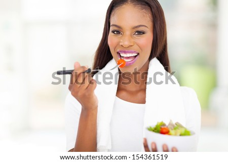 pretty african american woman eating salad - stock photo