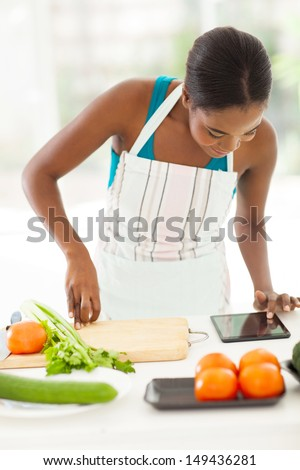 pretty african american woman looking at tablet computer for a recipe - stock photo