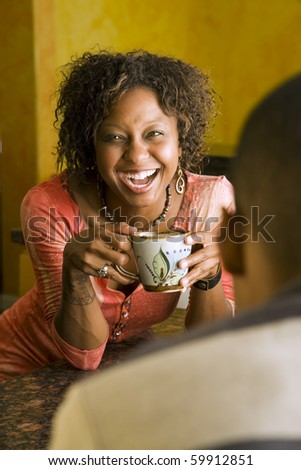 Pretty African-American woman talks to male in kitchen - stock photo