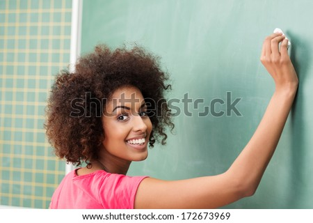 Pretty African American woman teacher in class writing on the blackboard as she teaches her students and turning to smile at the camera - stock photo