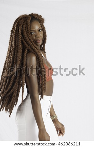 Pretty African American woman with long dreadlocks, looking thoughtfully at the camera