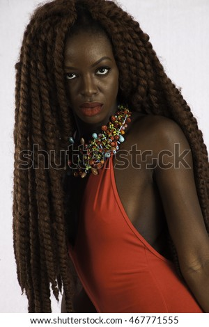 Pretty African American woman with long dreadlocks, wearing a red outfit,