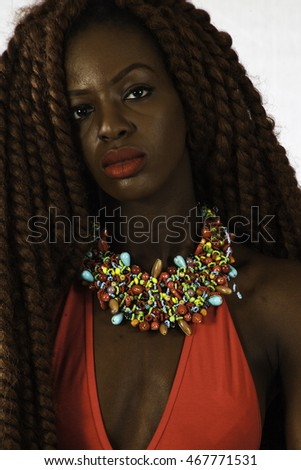 Pretty African American woman with long dreadlocks, wearing a red outfit, looking thoughtfully at the camera