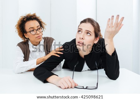 Pretty african american young businesswoman in glasses sitting and supporting her upset despaired colleague in office - stock photo