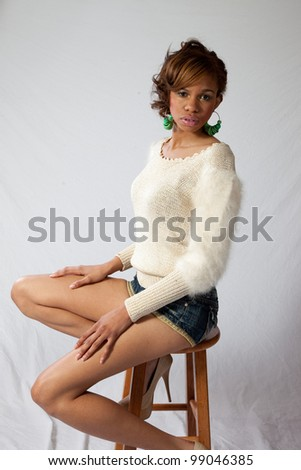 Pretty African American young woman in shorts and a white shirt sitting on a stool with a thoughtful expression