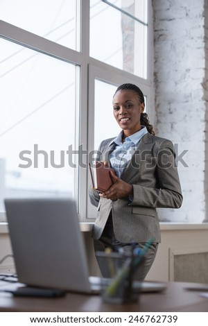 Pretty african business woman standing near window leaning windowsill at her office and taking notes in her diary while planning her day - stock photo