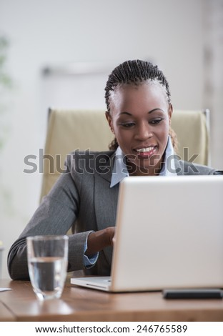 Pretty african business woman working on laptop in office - stock photo