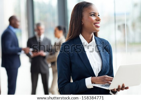 pretty african corporate worker using laptop - stock photo