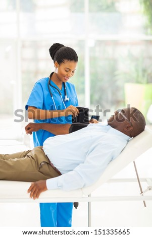 pretty african female nurse measuring senior patient blood pressure - stock photo