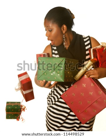 Pretty african girl holding her christmas presents and dropping two - stock photo