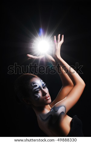 Pretty african girl with body-art on her face and flash in her hands - stock photo