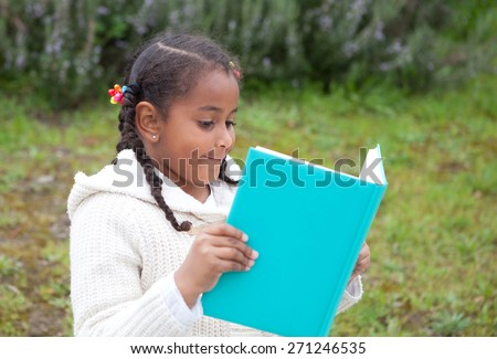Pretty african girl with winter clothes in the park reading a book - stock photo