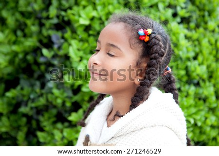 Pretty african girl with winter clothes in the park smelling - stock photo