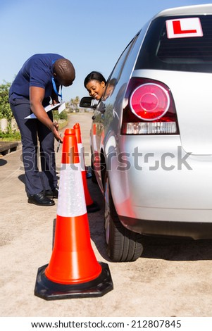 pretty african student driver with driving instructor learning to park a car - stock photo