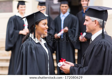 pretty african student receiving certificate from dean - stock photo