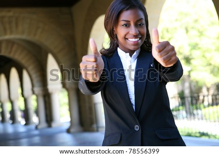 Pretty African Woman at College with thumbs up indicating success - stock photo