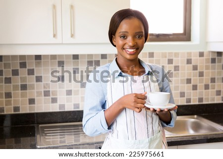 pretty african woman drinking coffee in kitchen - stock photo