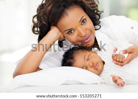 pretty african woman lying in bed with her daughter - stock photo