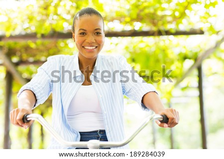 pretty african woman riding a bike outdoors - stock photo