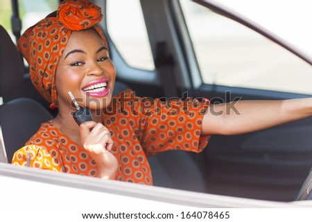 pretty african woman showing car key inside new vehicle - stock photo